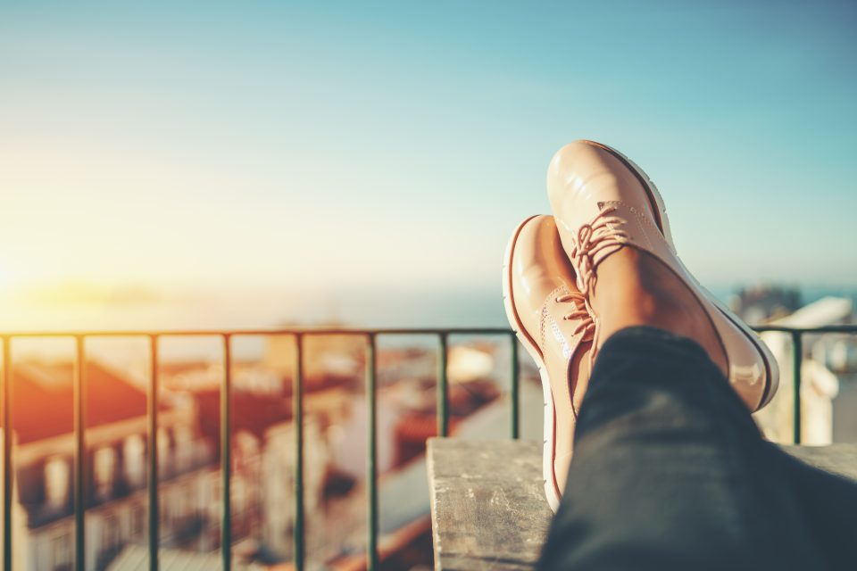Shoed feet of someone reclining on a balcony