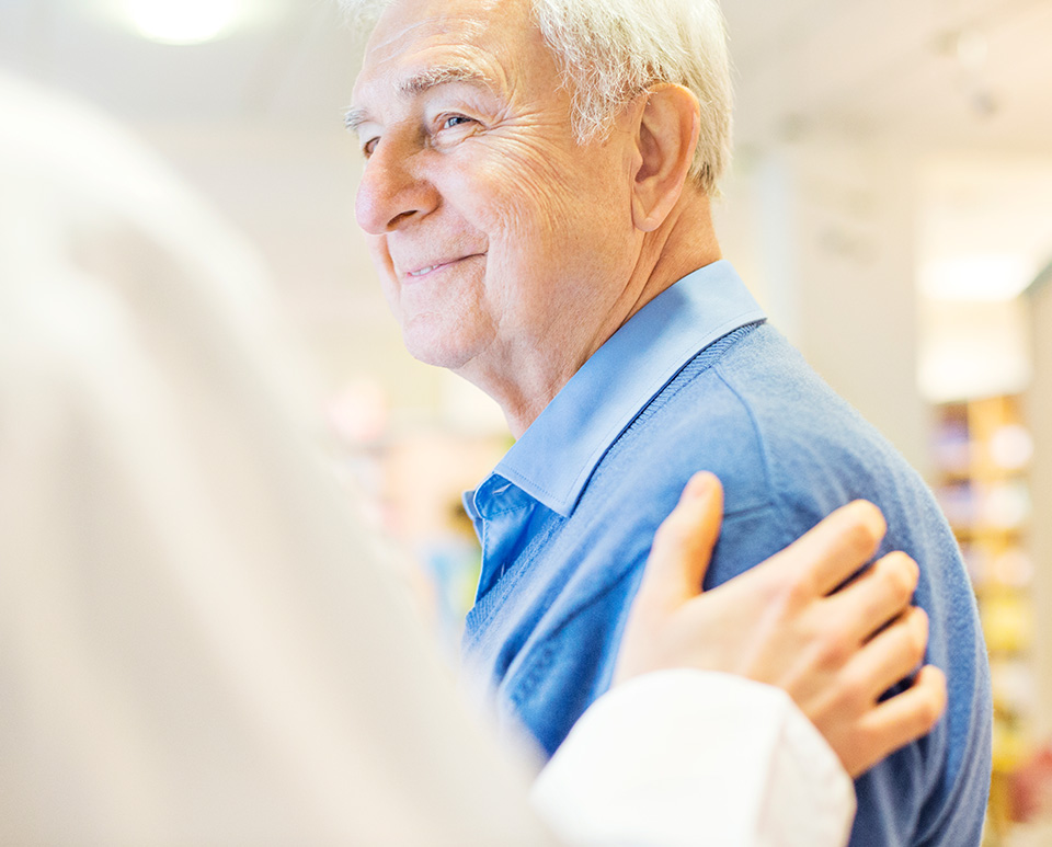 Older male patient with hand on his shoulder