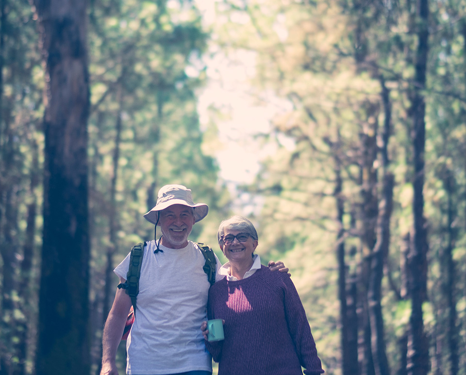 Older white couple walking through forest smiling